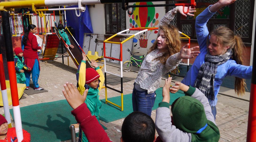 Två Projects Abroad ungdomsvolontärer leker lärande lekar på en förskola i Nepal